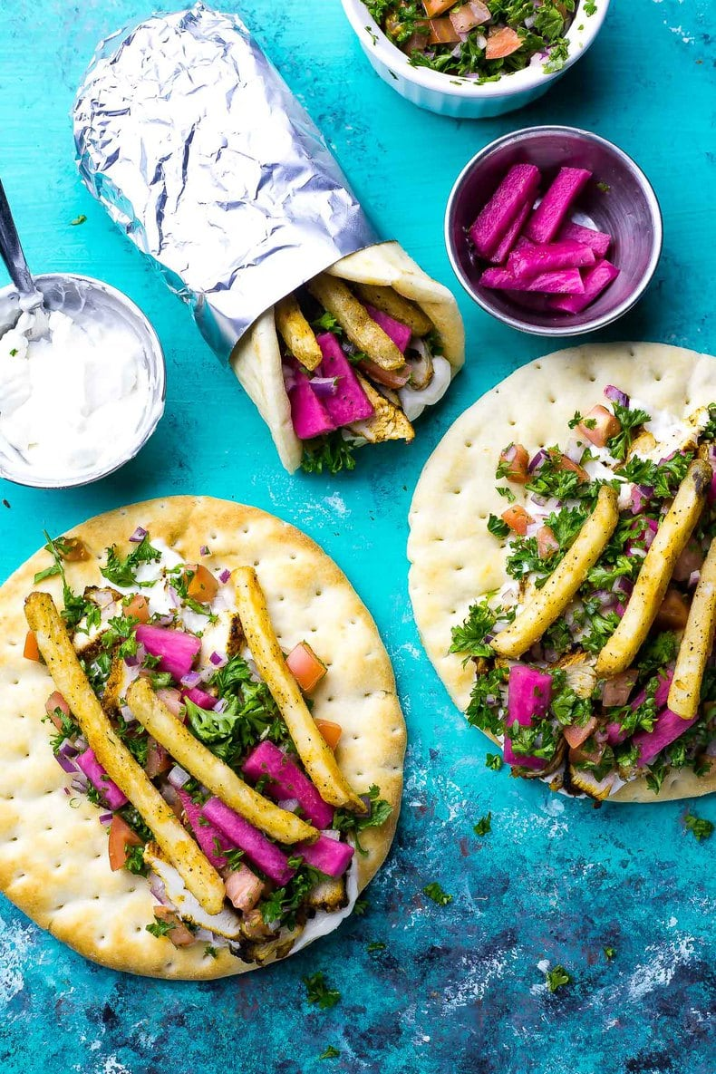 This Chicken Shawarma recipe comes complete with taboule, homemade vegan garlic sauce and pickled turnips all stuffed into a warm pita. It's a surprisingly healthy copy cat!