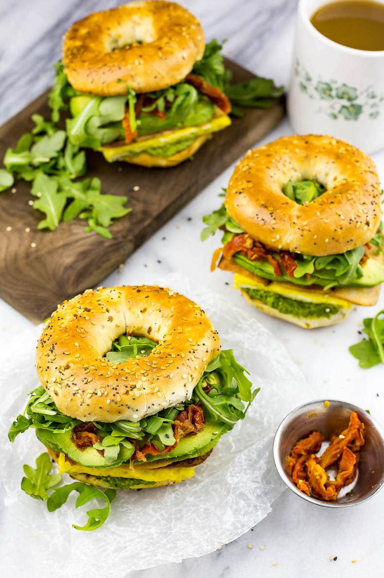 These Pesto Bagel Breakfast Sandwiches come fully loaded with scrambled eggs, turkey bacon, arugula, sundried tomatoes, avocado and a quick basil pesto in between an everything bagel!