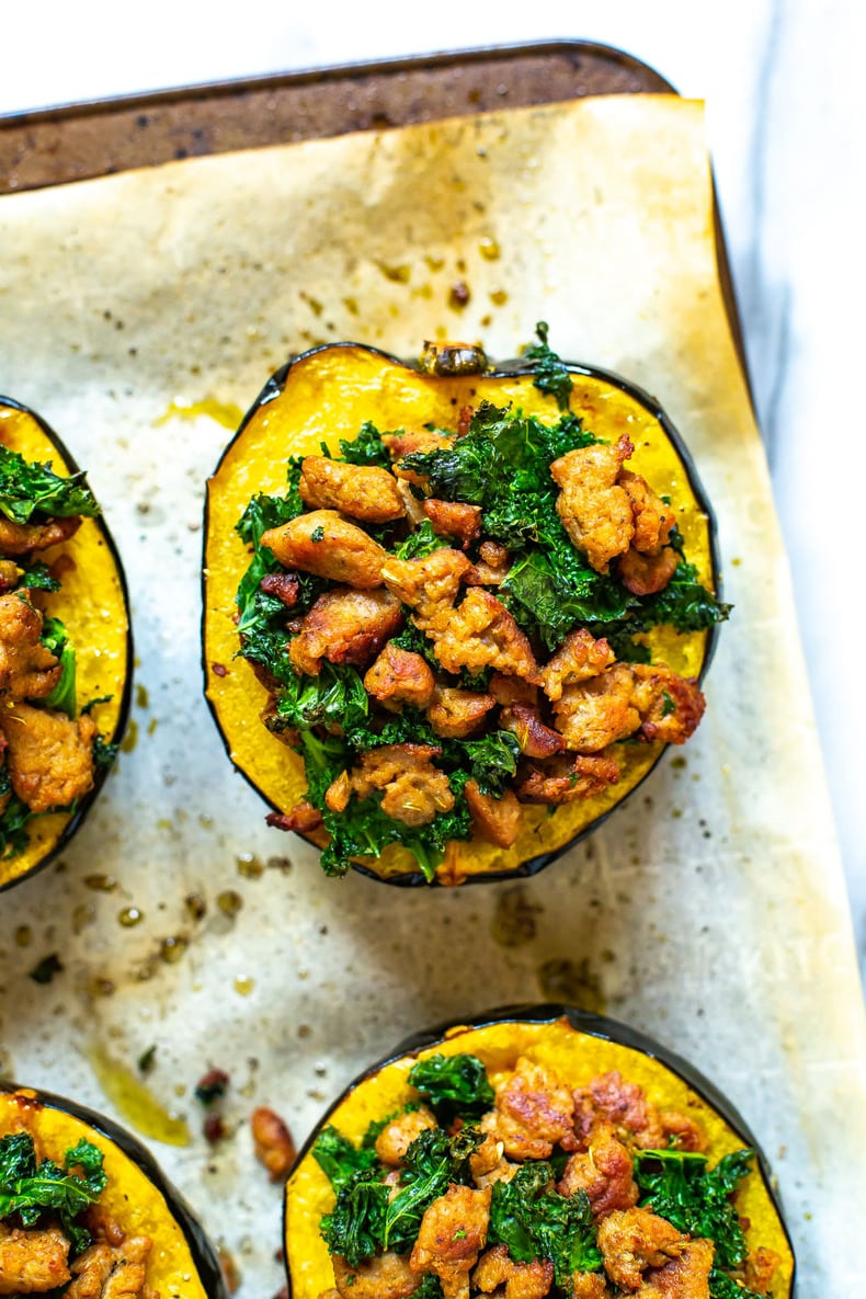 winter squash on baking sheet, with sausage and kale filling